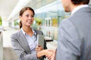 Businesswoman shaking hand to partner