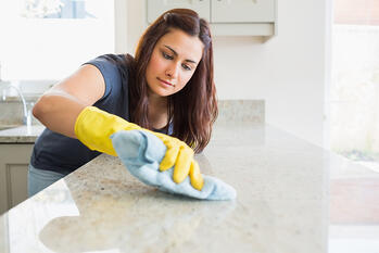 Concentrated woman scrubbing the bar in kitchen